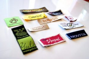 Szövött címke készítés egyedi elképzelések szerint, a megrendelő igényei alapján, grafikai tervezéssel, a legjobb minőségben, akár rövid határidővel is.